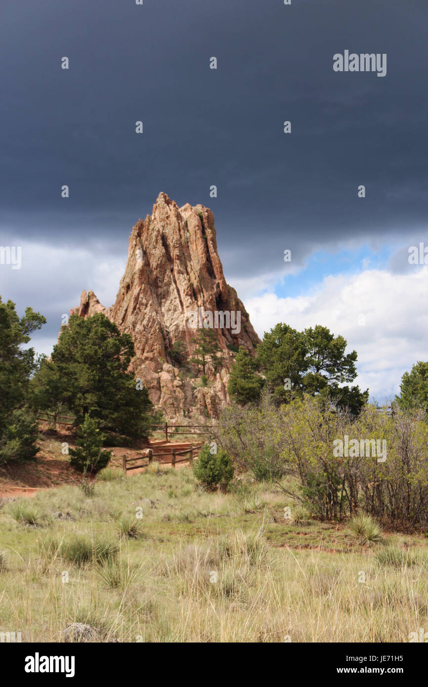 Rock formation and vegetation along a hiking trail at Garden of the Gods in Colorado Springs, Colorado, USA, under - Stock Image