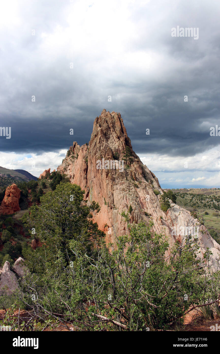 Rock formations and vegetation along a hiking trail at Garden of the Gods in Colorado Springs, Colorado, USA, under - Stock Image