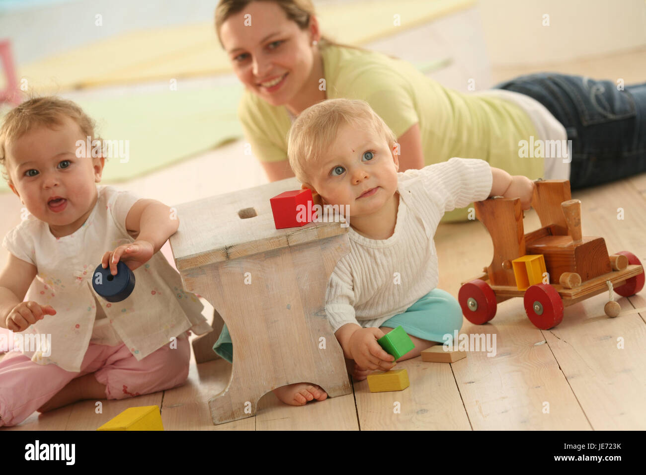 Babies, 9 months, mother, play, wooden toys, toys, dress, blond, discoveries, friends, reach, group, Indoor, boy, - Stock Image