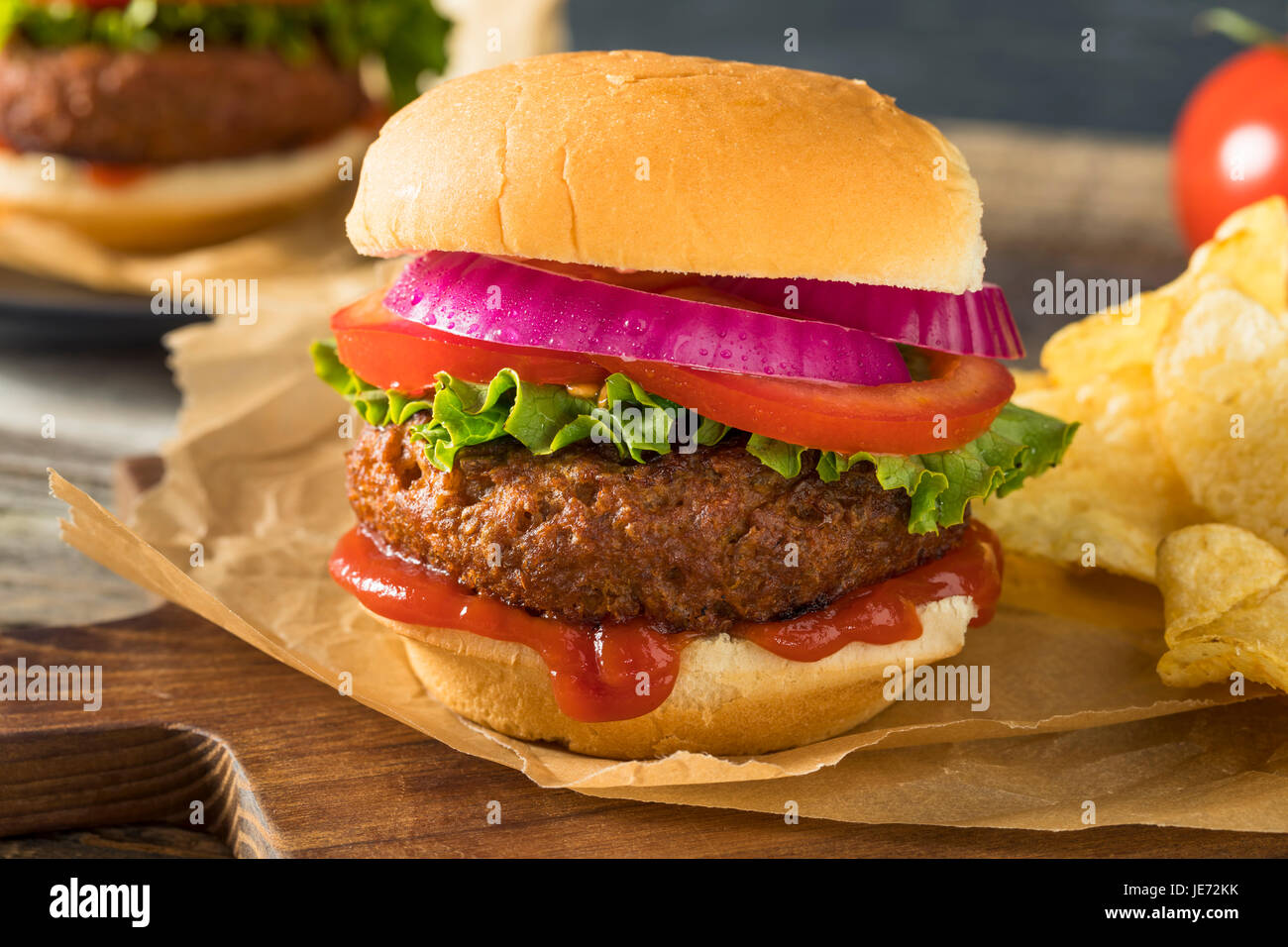 Healthy Vegan Vegetarian Meat Free Burger with Lettuce Tomato and Onion - Stock Image