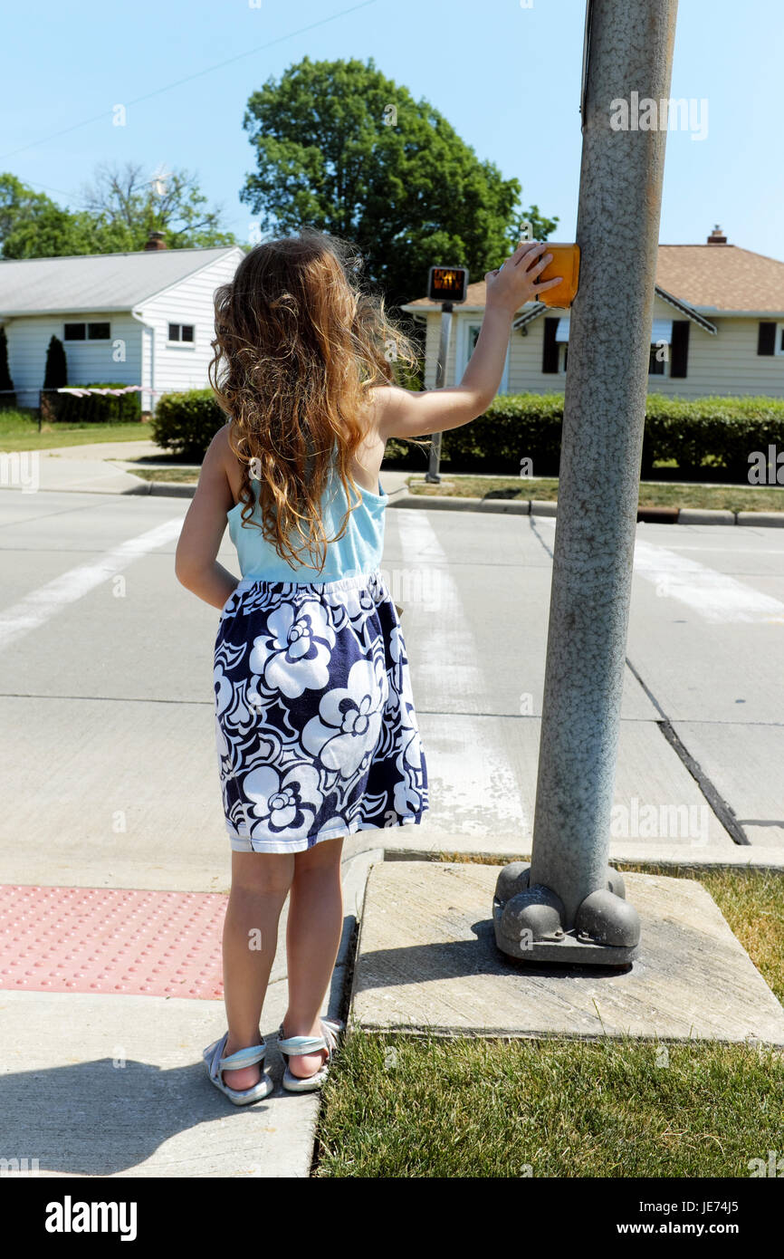 Five-year old girl stands at crosswalk pressing the button waiting patiently for the crosswalk sign to indicate - Stock Image