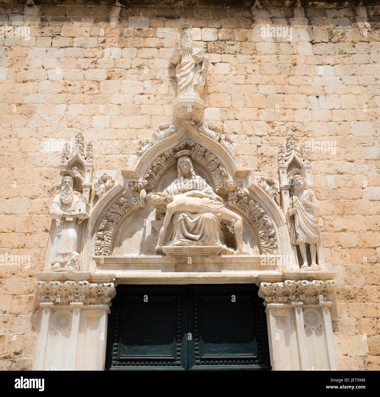 Carved stone pediment depicting the dead Christ and Mary Magdalene on a door on the Franciscan monastery on the - Stock Image