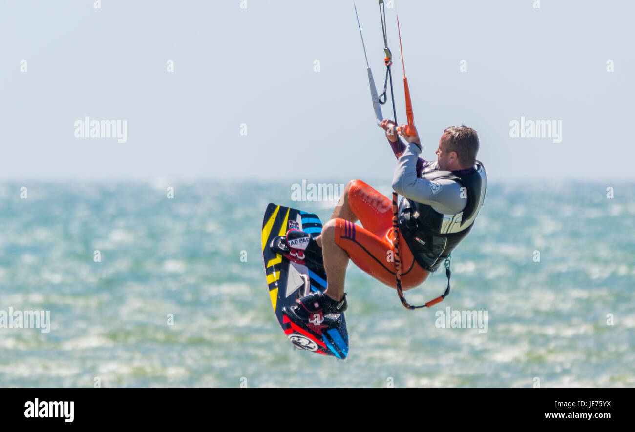 Kitesurfing. Kitesurfer flying in the air as he does a stunt while at sea on a windy day. - Stock Image