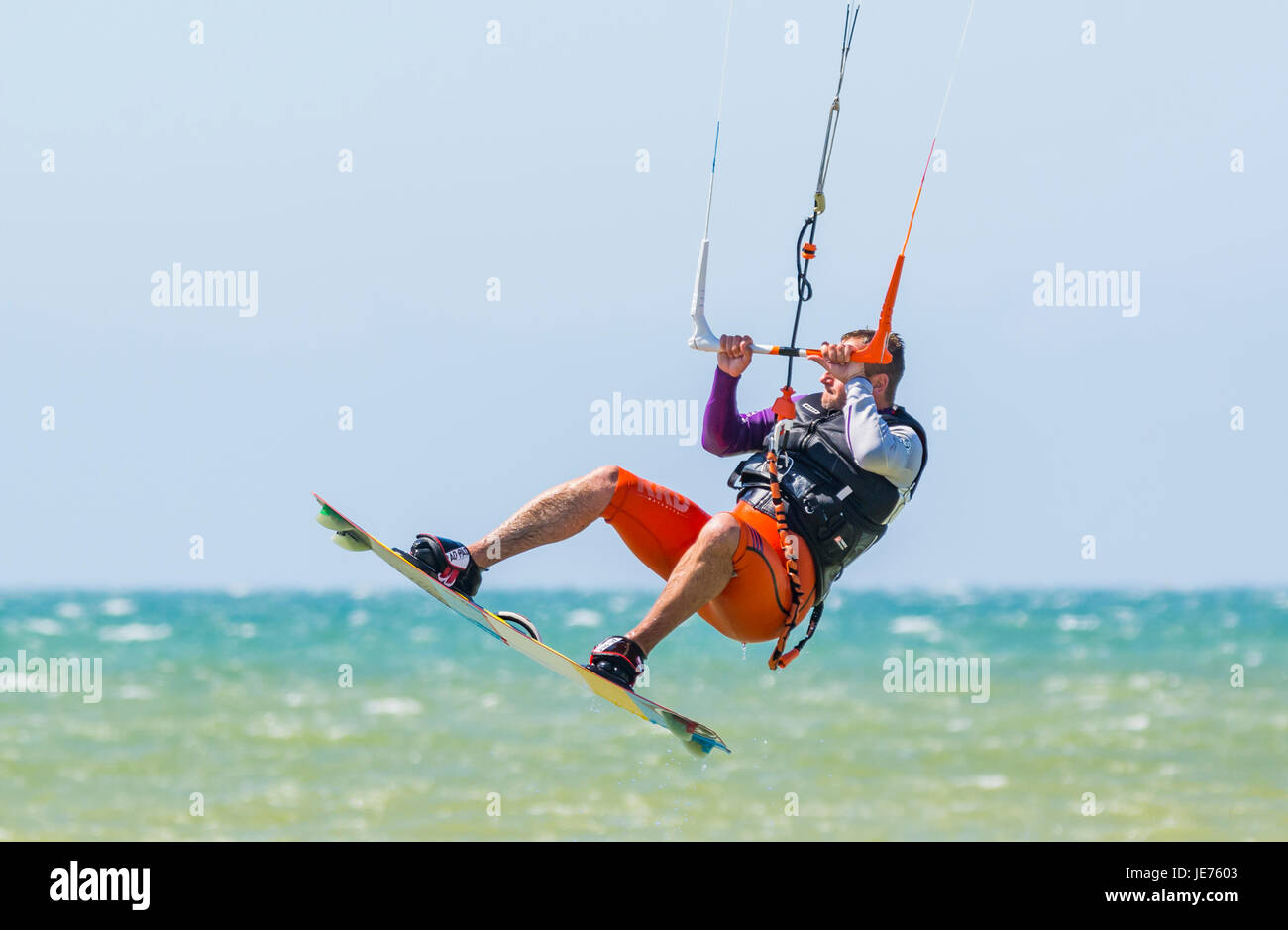 Kitesurfer flying in the air as he does a stunt while at sea on a windy day. - Stock Image