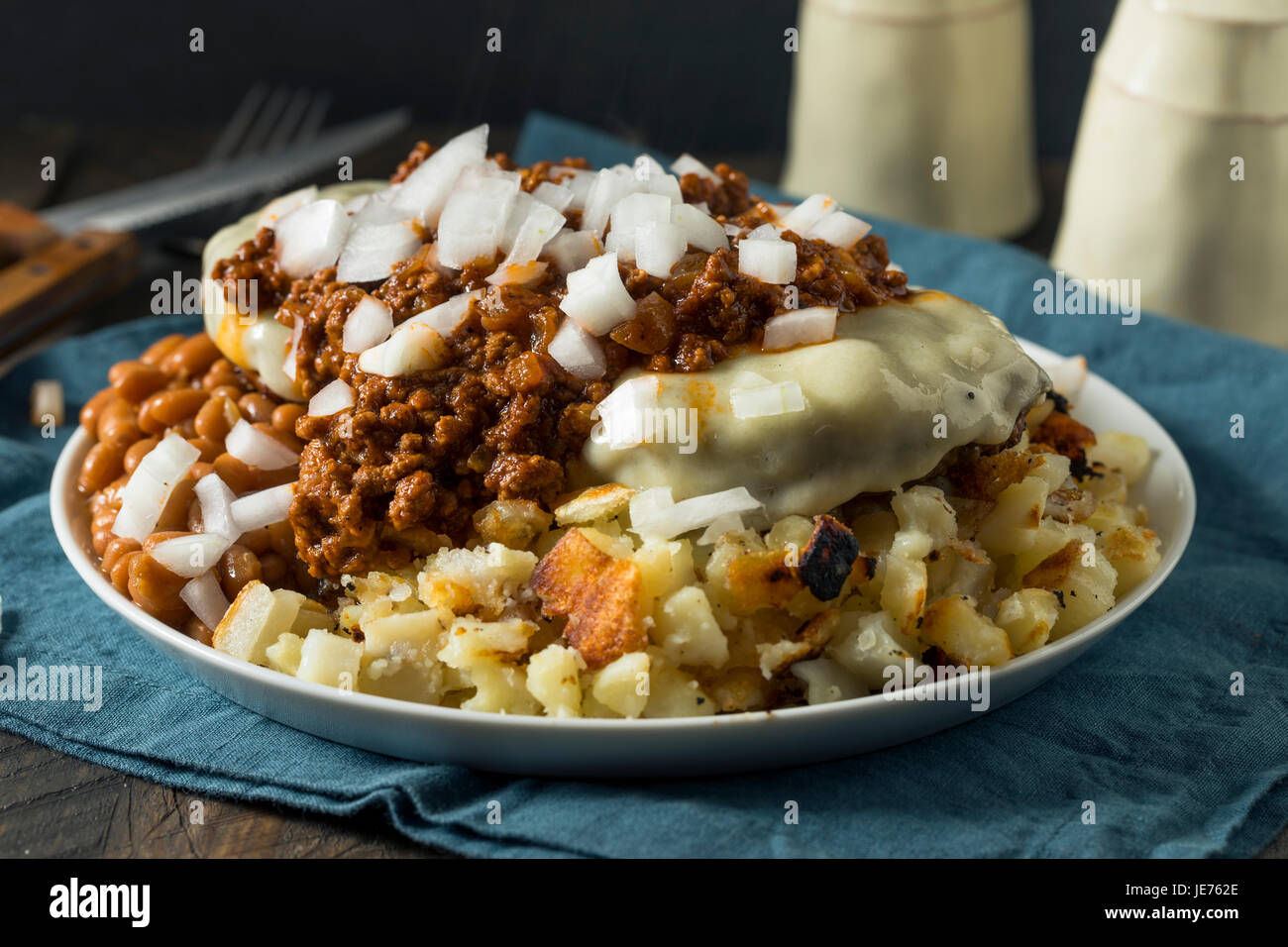 Unhealthy Homemade Beef Garbage Trash Plate with Potatoes Beans Macaroni Salad and Cheeseburgers - Stock Image