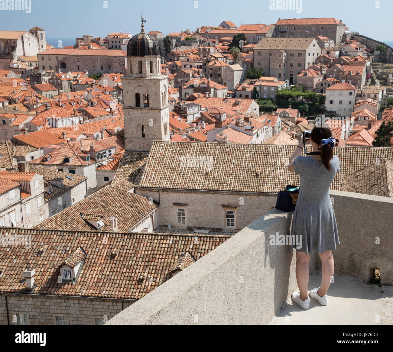 An Asian tourist taking a photograph of the medieval city of Dubrovnik on the Dalmation coast of Croatia - Stock Image