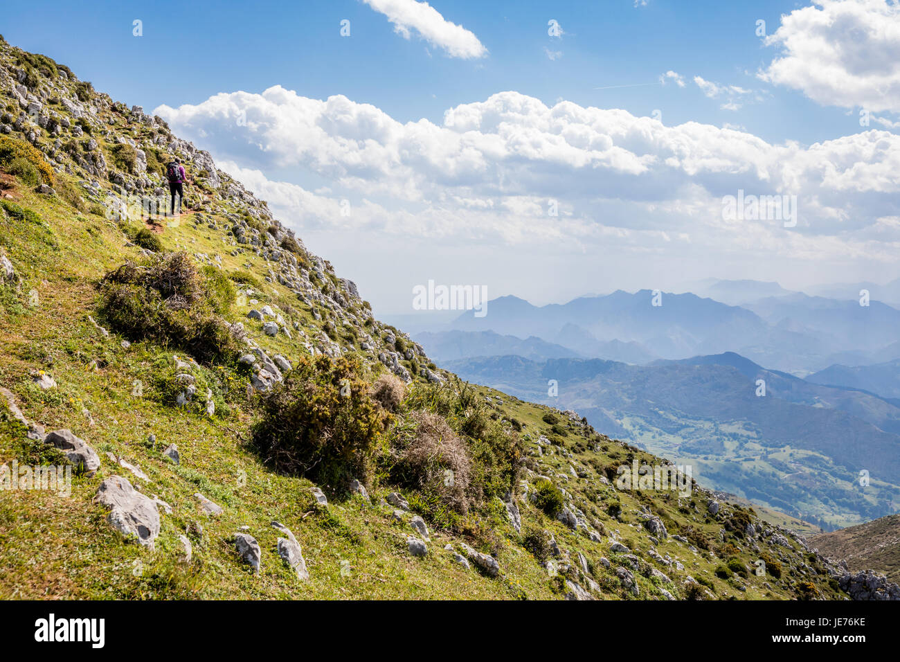 A female walker climbing the steep slope to the rocky summit of Pico Pienzu in the Picos de Europa in northern Spain - Stock Image