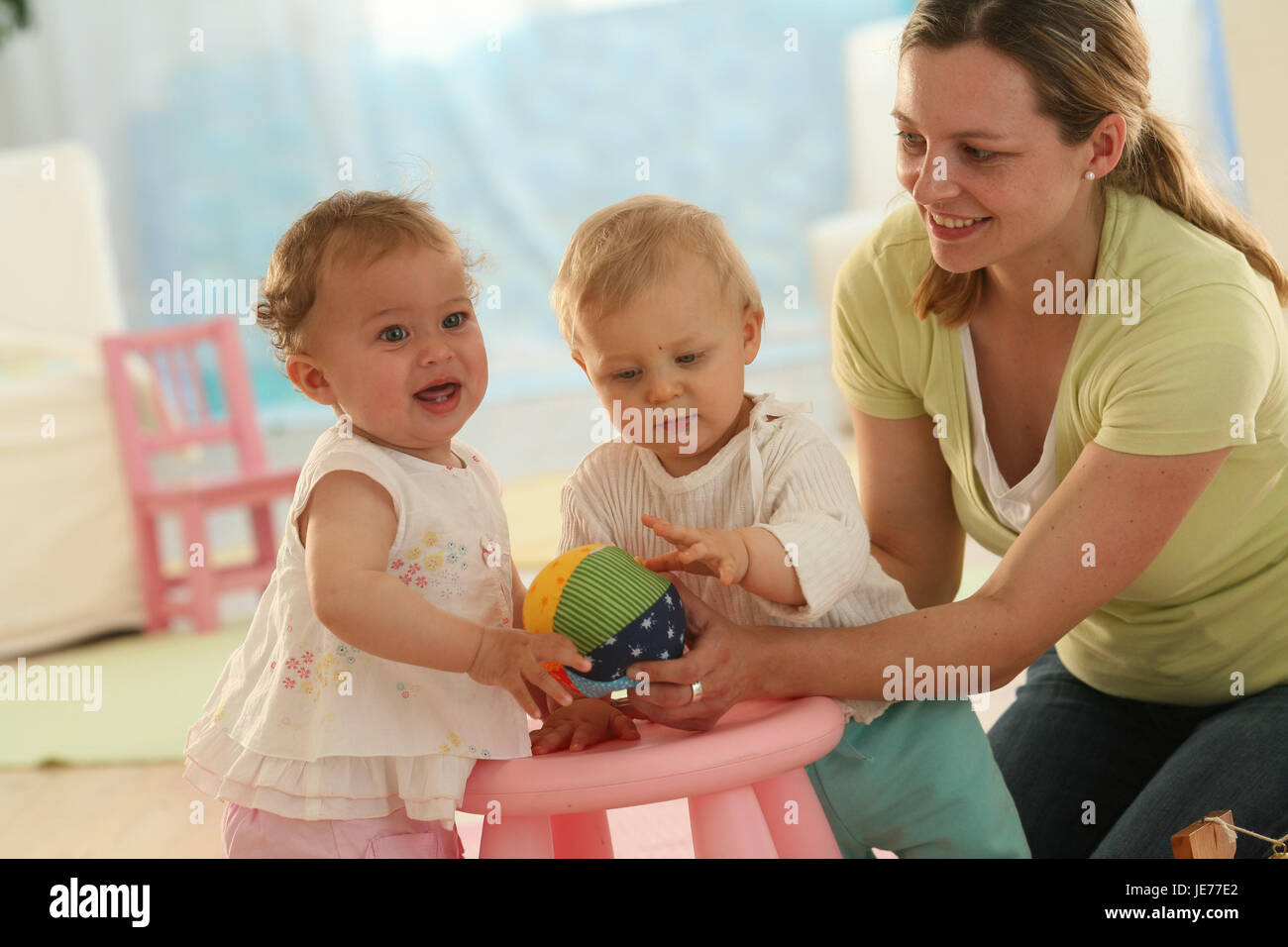 Babies, 9 months, mother, ball, play, toys, dress, blond, discoveries, friends, reach, group, Indoor, boy, person, - Stock Image