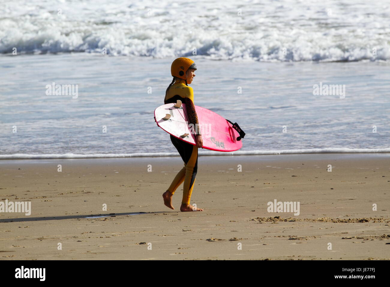A young preteen surfer girl going surfing. - Stock Image