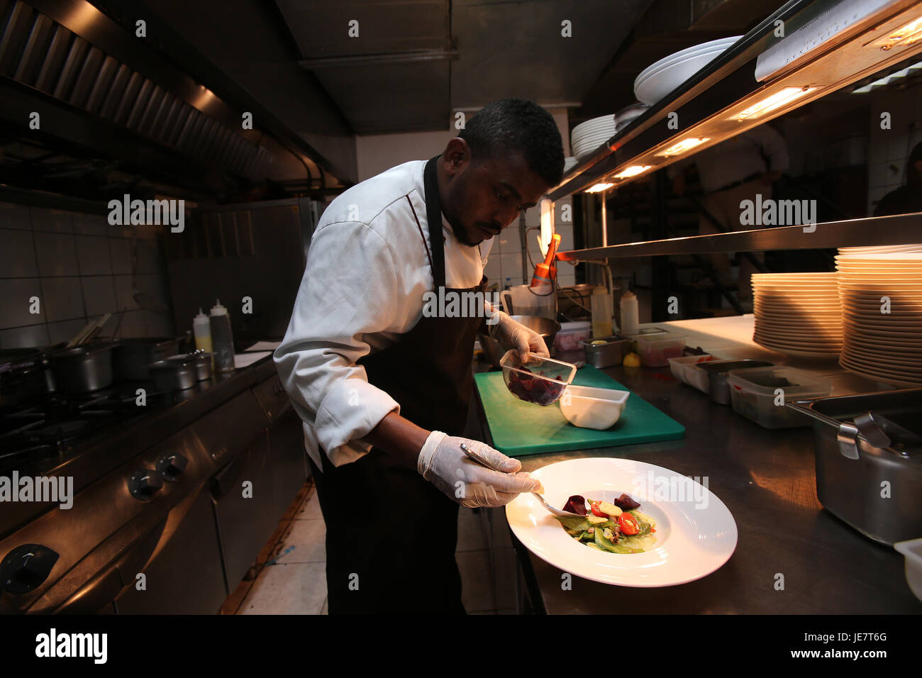 Athens, Greece. 22nd June, 2017. 25-year-old refugee chef Hassan from Somalia, prepares dishes for customers in - Stock Image