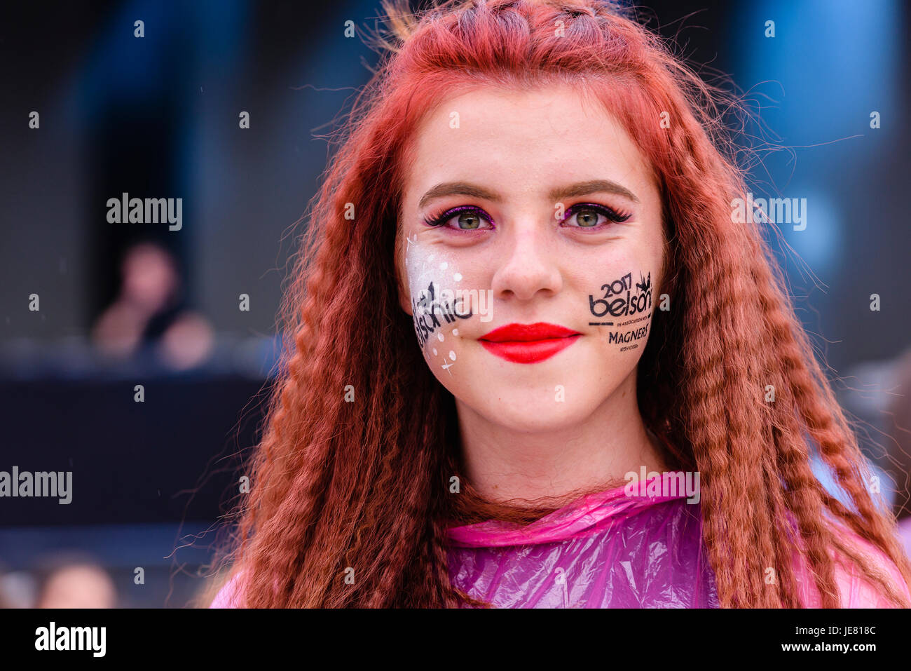 Belfast, Northern Ireland. 22/06/2017 - A pretty young lady with red hair and lipstick has Belsonic stencils on - Stock Image