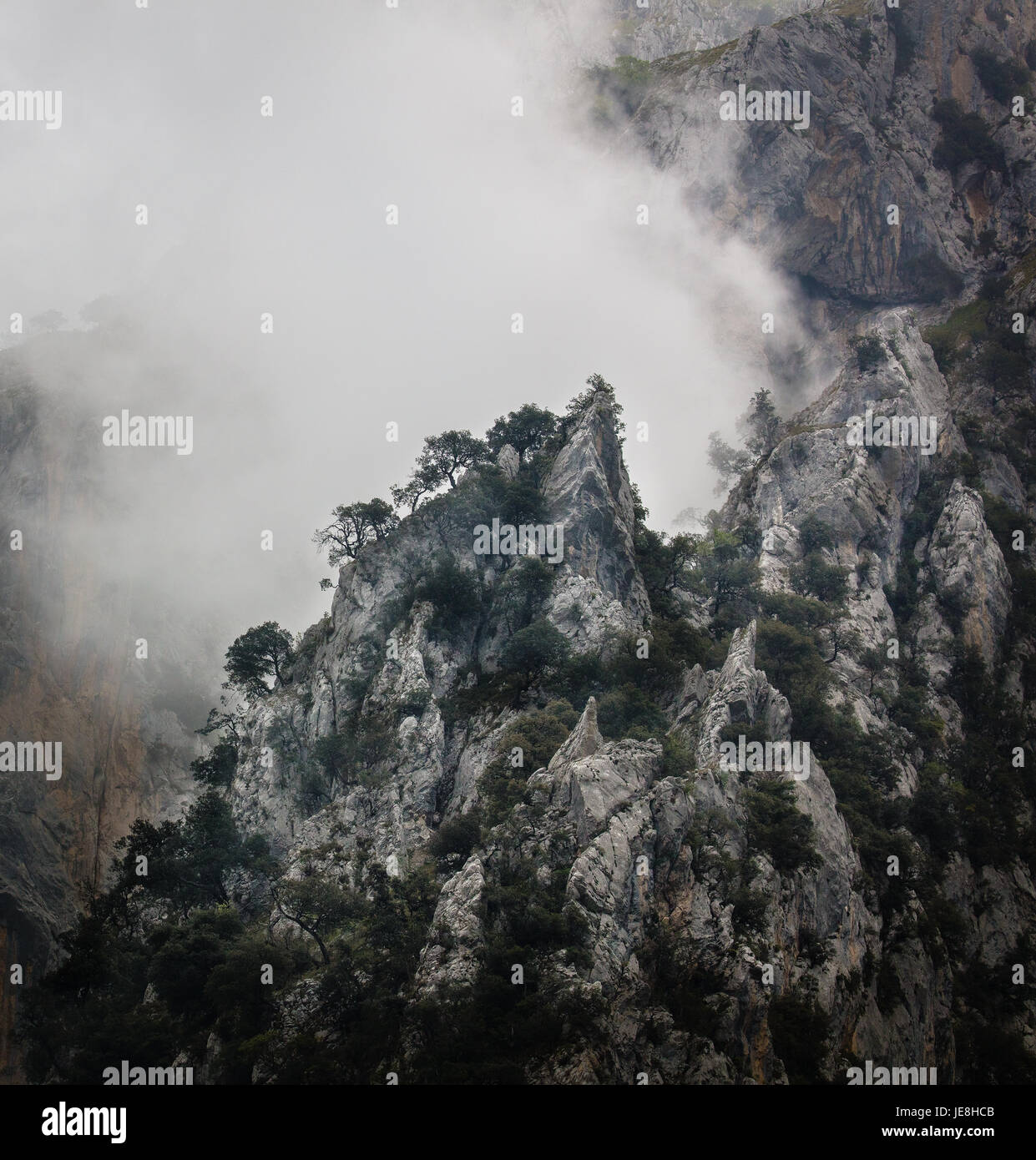 Low cloud and mist swirling round limestone peaks of the Cares Gorge in the Picos de Europa in Northern Spain - Stock Image