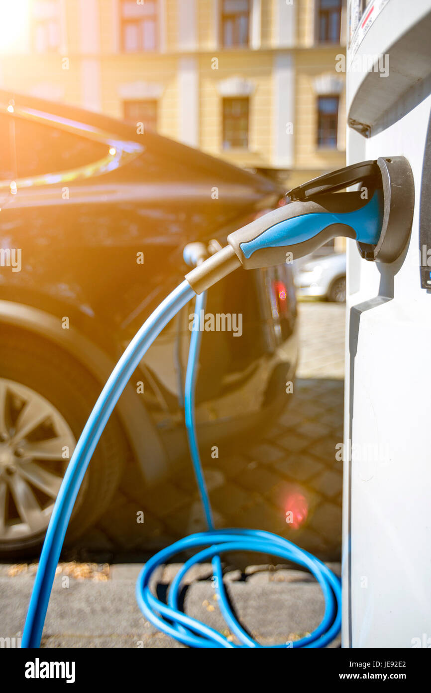Close up of the power supply plugged into an electric car being charged - Stock Image