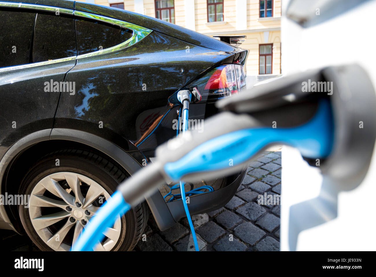 Close up of the power supply plugged into an electric car being charged Stock Photo