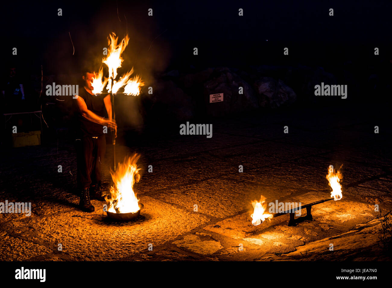 Street artist with a burning stick and eyes closed preparing to present his fire show - Stock Image