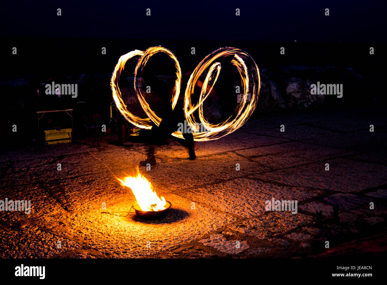 Street artist with a burning stick during his dangerous fire show - Stock Image
