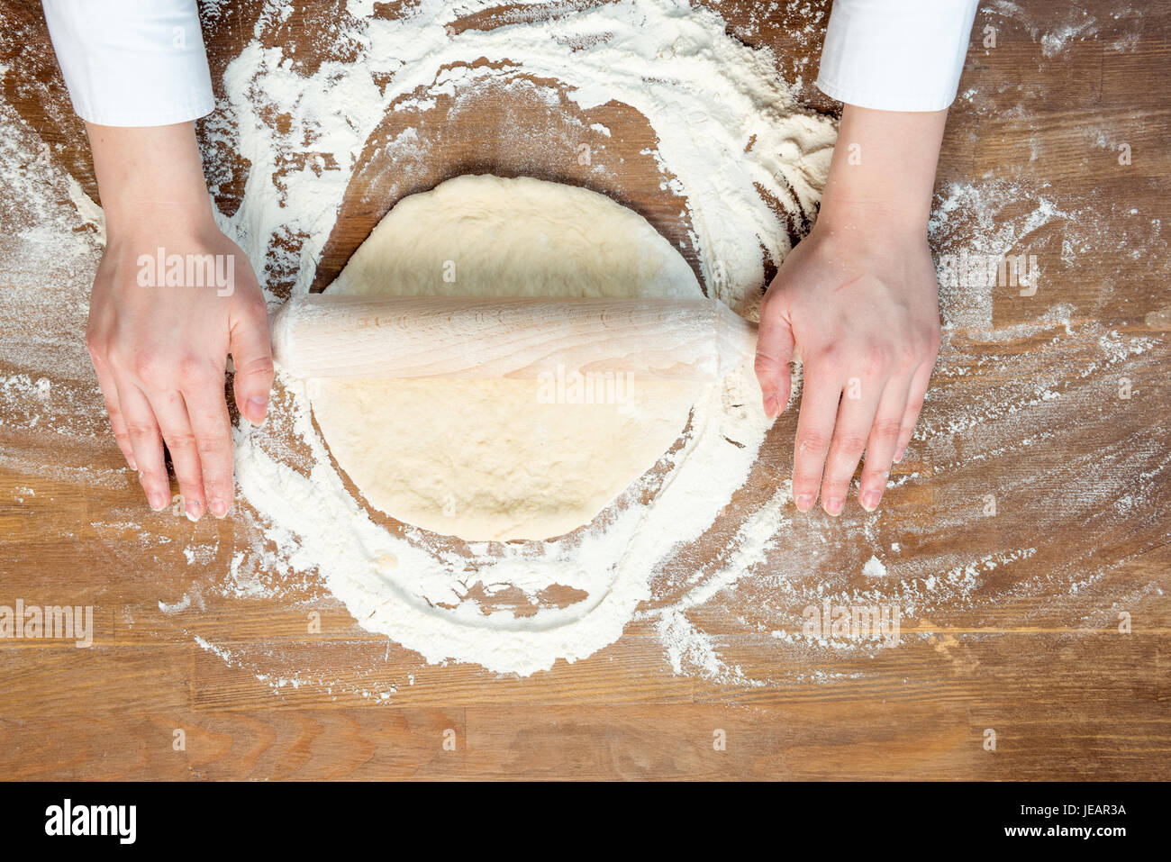 top view of child making pizza dough on wooden tabletop - Stock Image