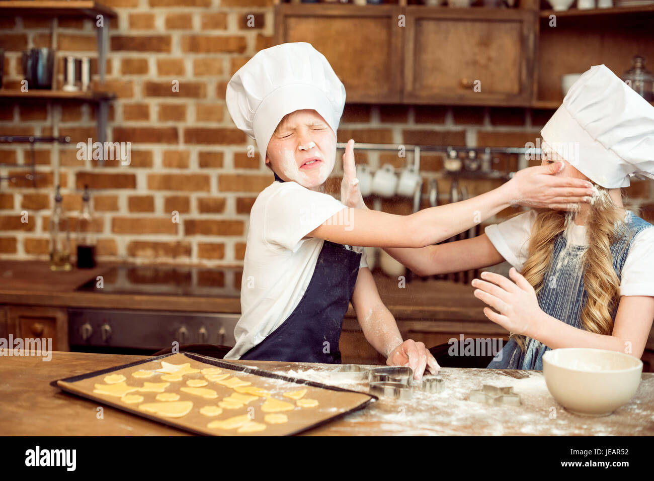 little boy and girl playing with flour while making shaped cookies - Stock Image