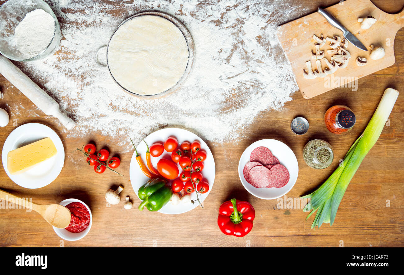 top view of pizza ingredients, tomatoes, salami and mushrooms on wooden tabletop - Stock Image
