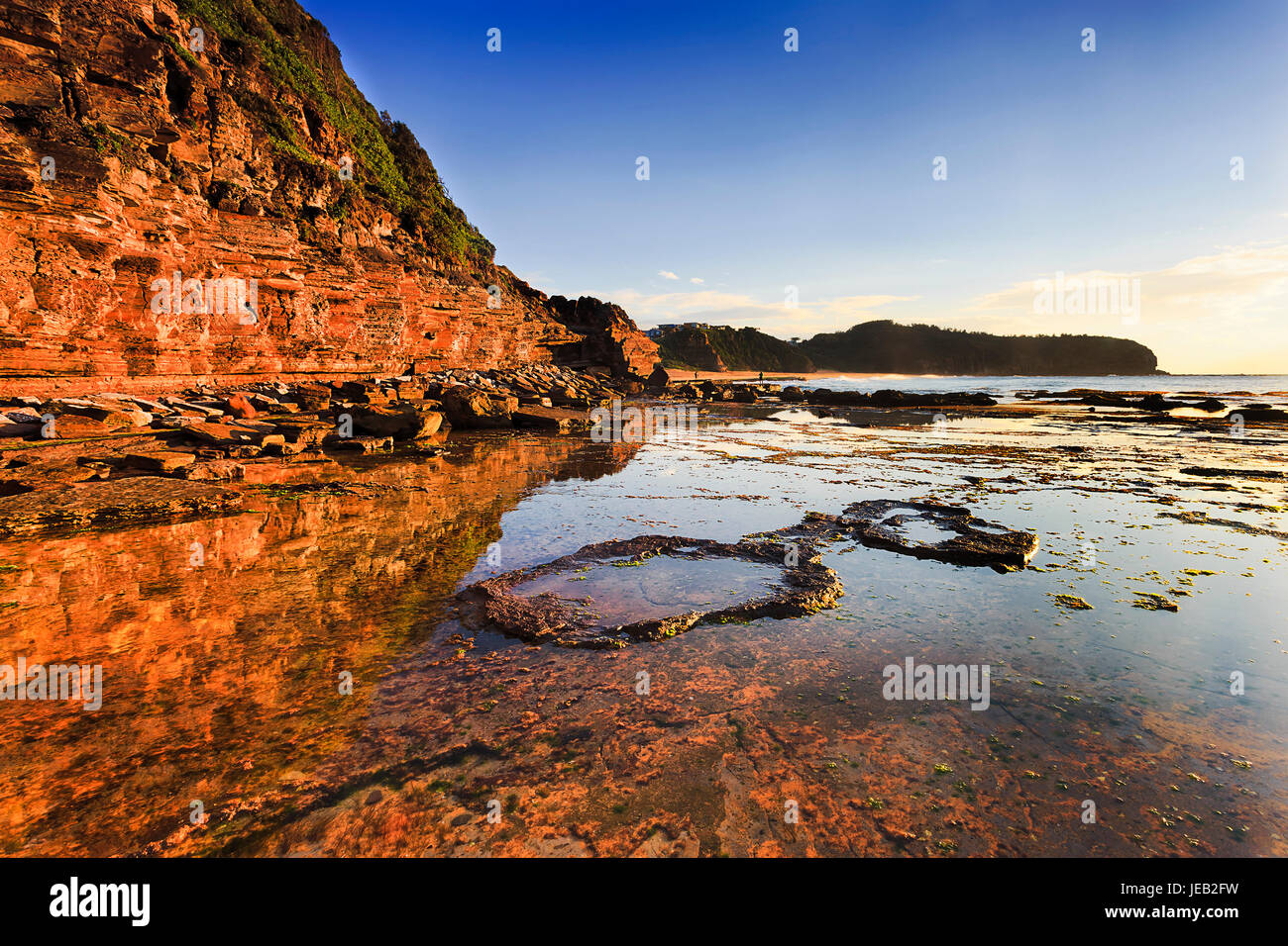 Warm illuminated by rising morning sune the rock cliff headland of Narrabeen beach off Australian pacific coast. - Stock Image