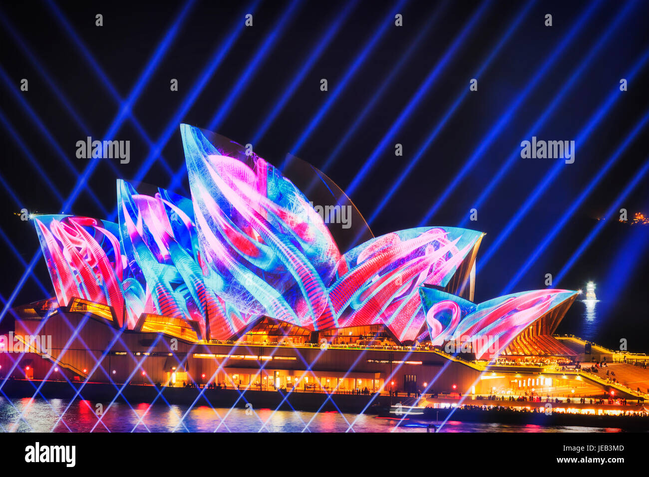 Sydney, Australia - 12 June 2017: Sydney Opera house behind crossing of blue light beams under colourful projection - Stock Image