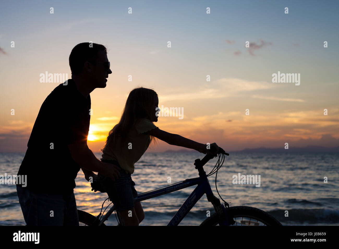 Father and daughter  playing on the beach at the sunset time. Concept of friendly family. - Stock Image