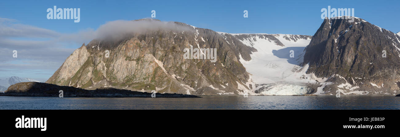 The high cliffs of Hamiltonbreen in Spitzbergen, split by a small glacier, with the peak almost hidden by a small - Stock Image