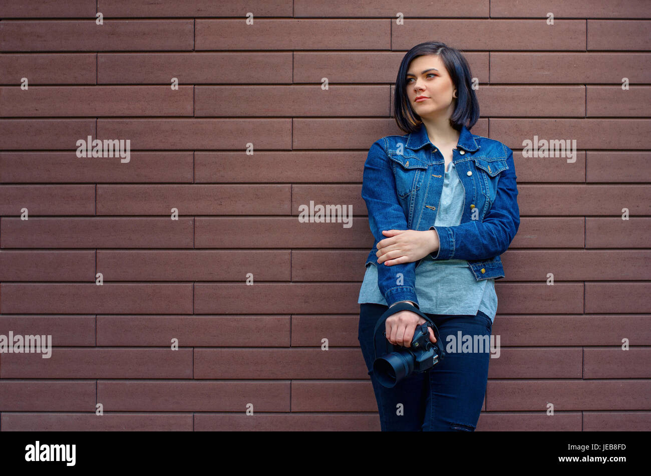 Thoughtful brunette caucasian girl  in a blue jeans jacket with digital camera in hands near a brown  textured brick - Stock Image