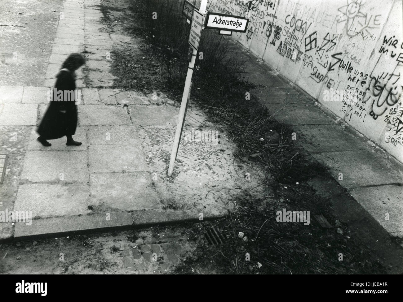 A lady walks towards the Berlin Wall at the junction of Ackerstraße and Bernauerstraße in Oct 1987 - Stock Image