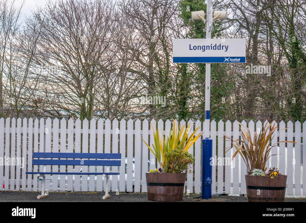 Longniddry train station platform sign with benches, flowerpots and white picket fence, East Lothian, Scotland, - Stock Image