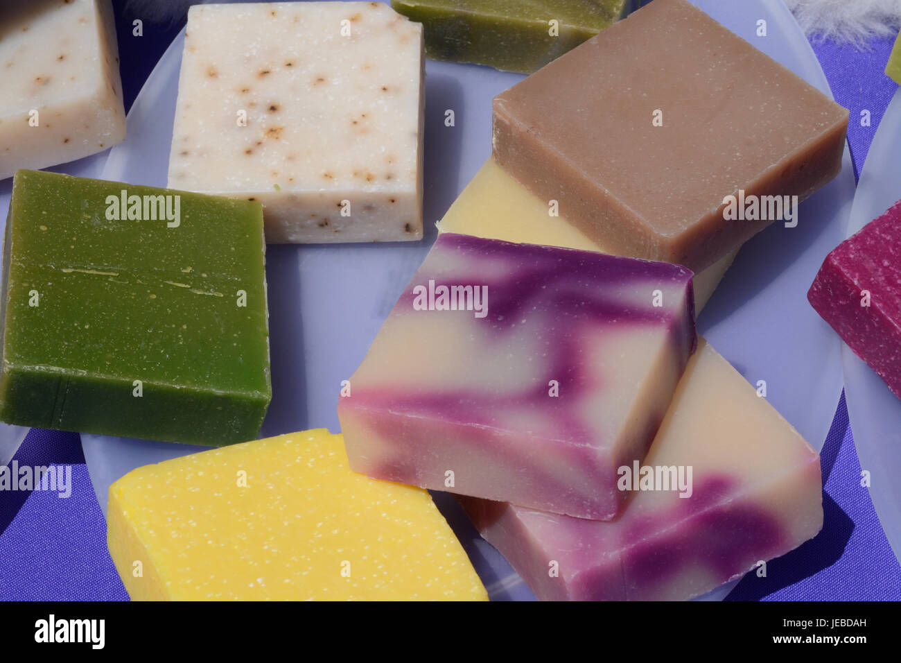 Colorful handmade beeswax soap squares on plates - Stock Image