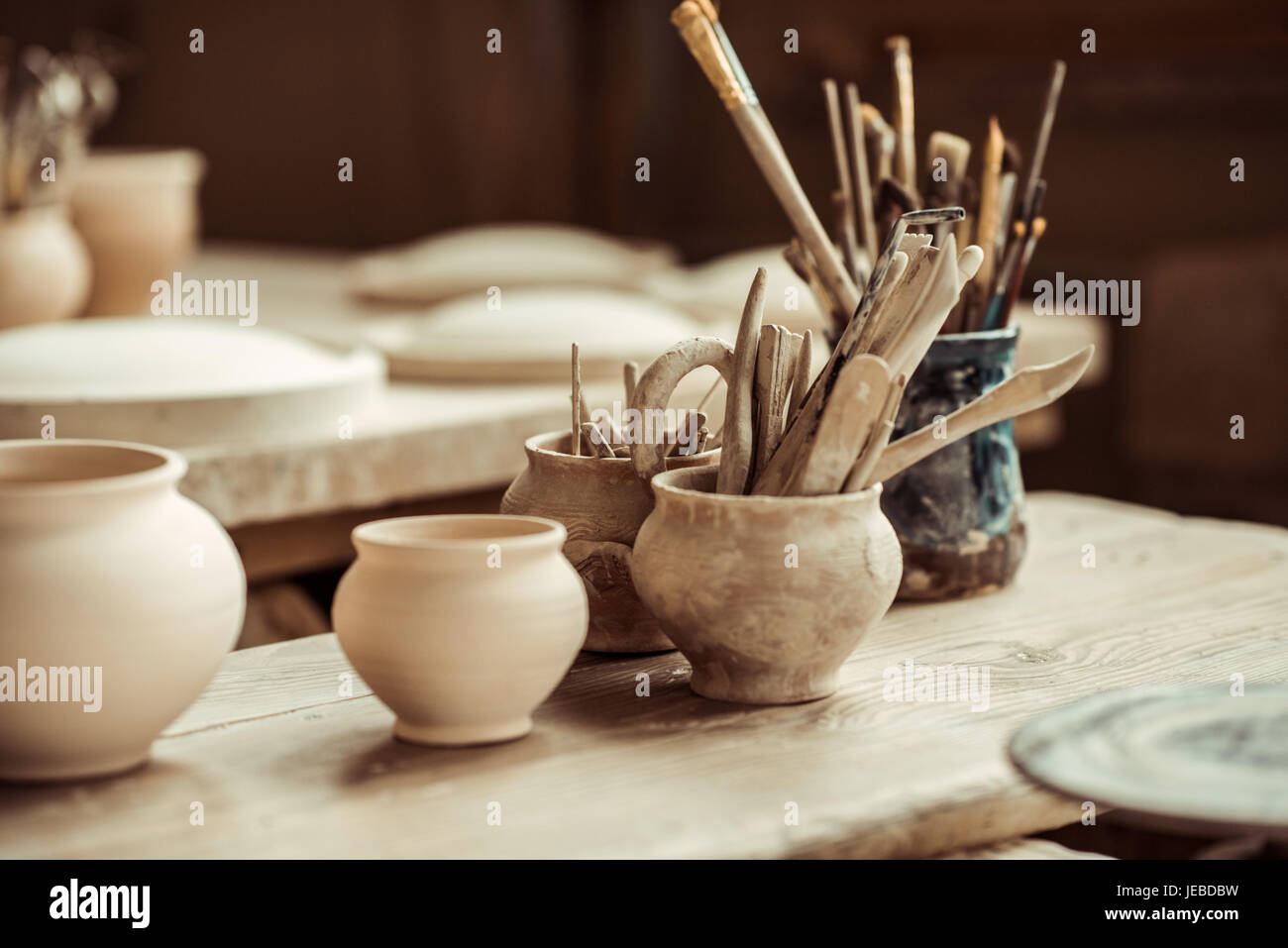 Close up of paint brushes with pottery tools in bowls on table - Stock Image