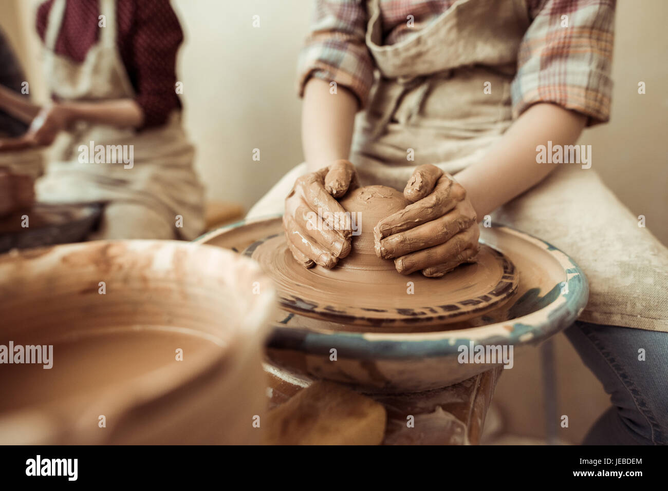 Close up of child hands working on pottery wheel at workshop - Stock Image