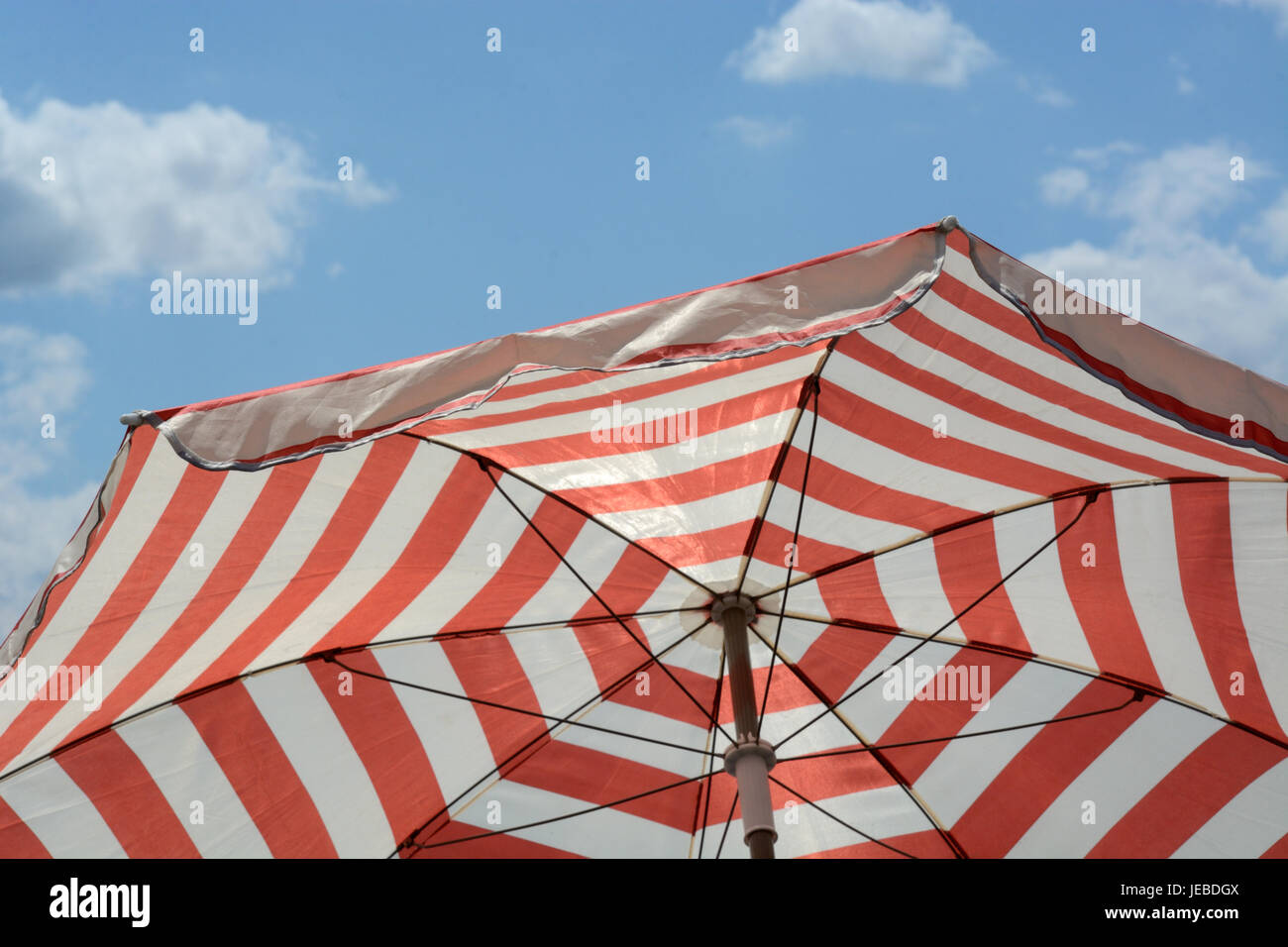 Red striped umbrella parasol to provide shade and sun protection against blue sky with light clouds - Stock Image