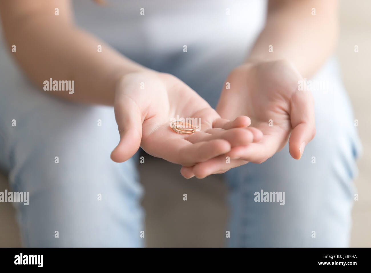 Close up image of golden ring in womans hands - Stock Image