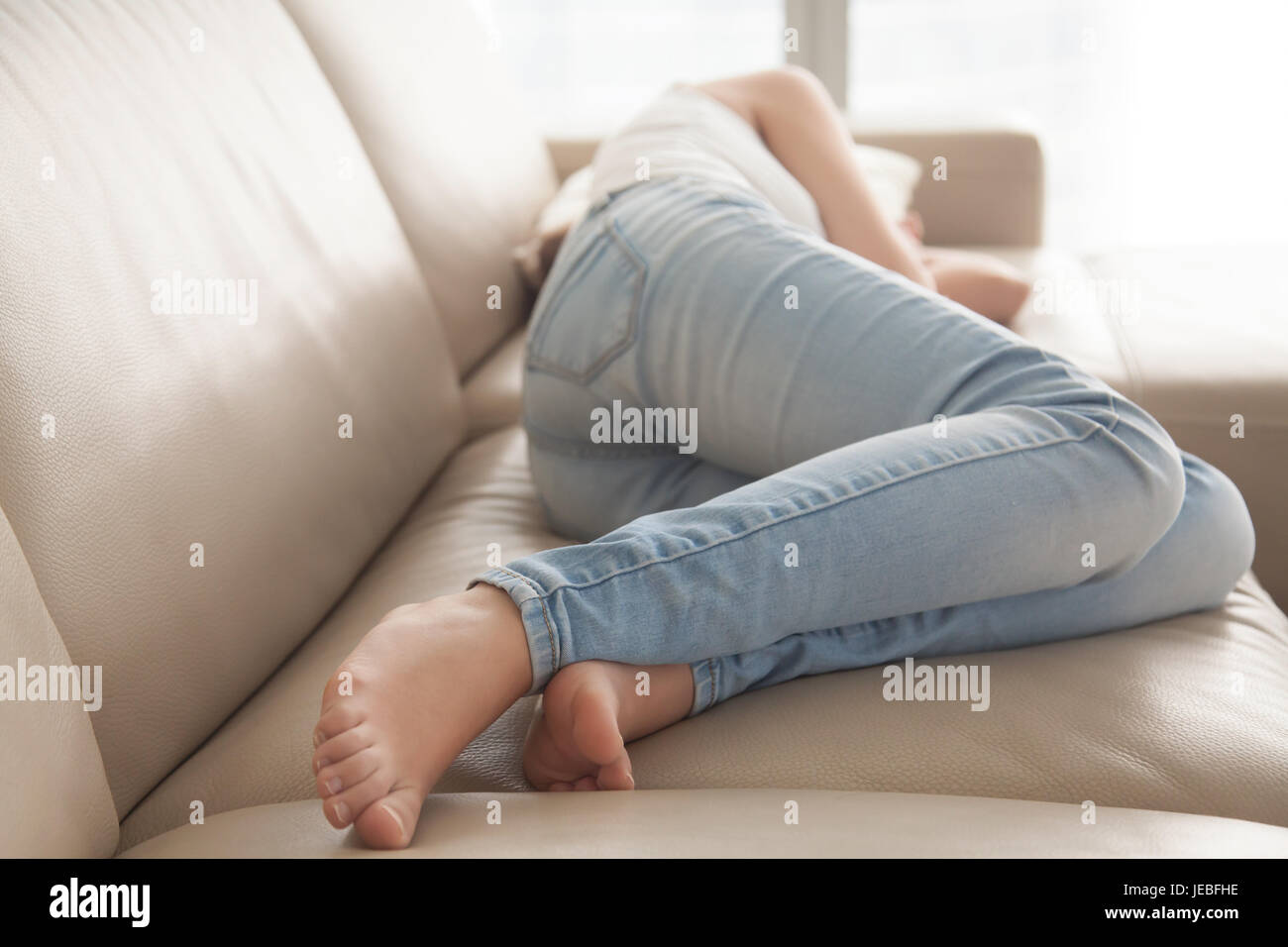Stressed woman lying upset on sofa at home - Stock Image