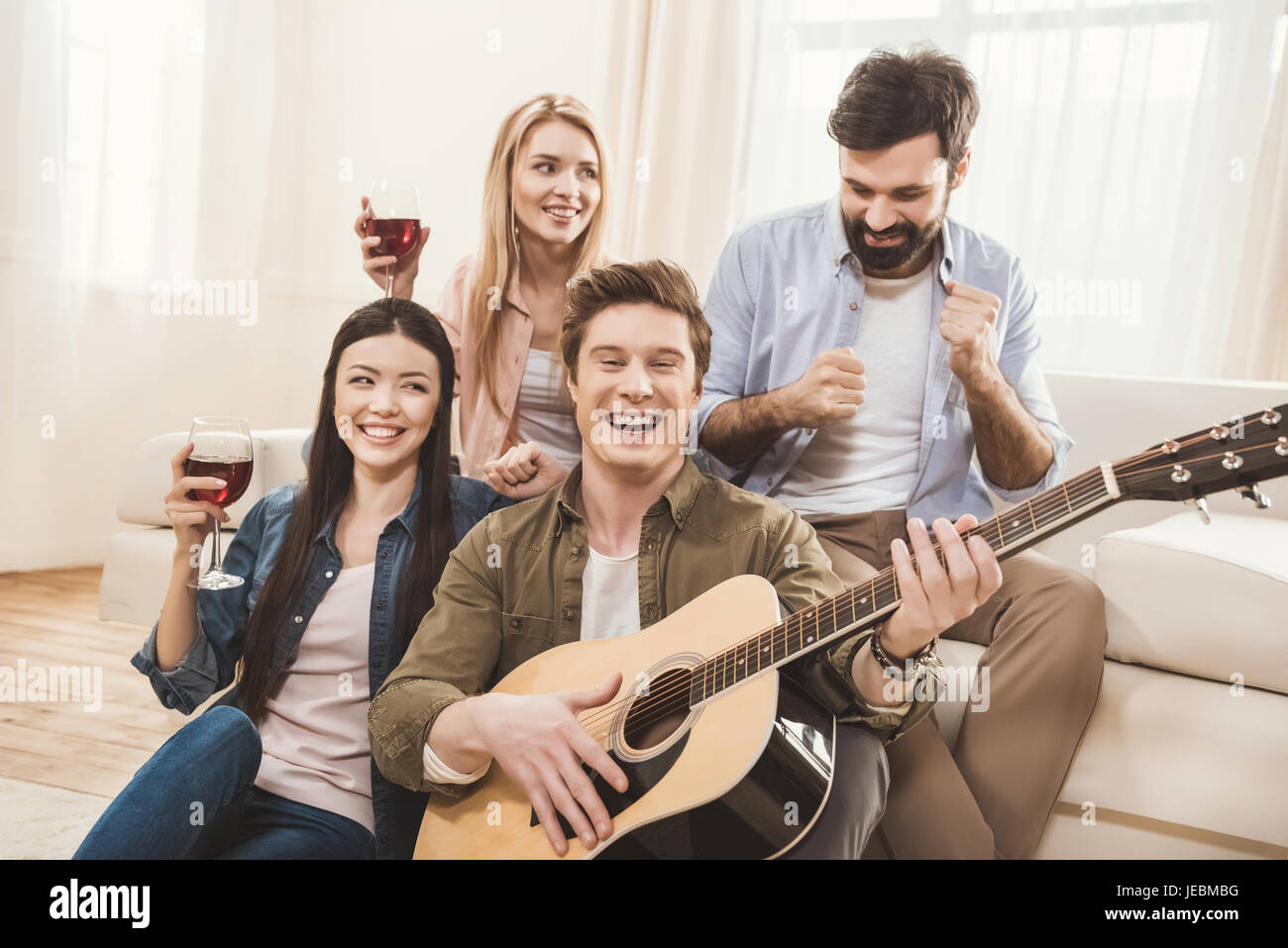 Diverse people partying together at dining room, playing acoustic guitar - Stock Image
