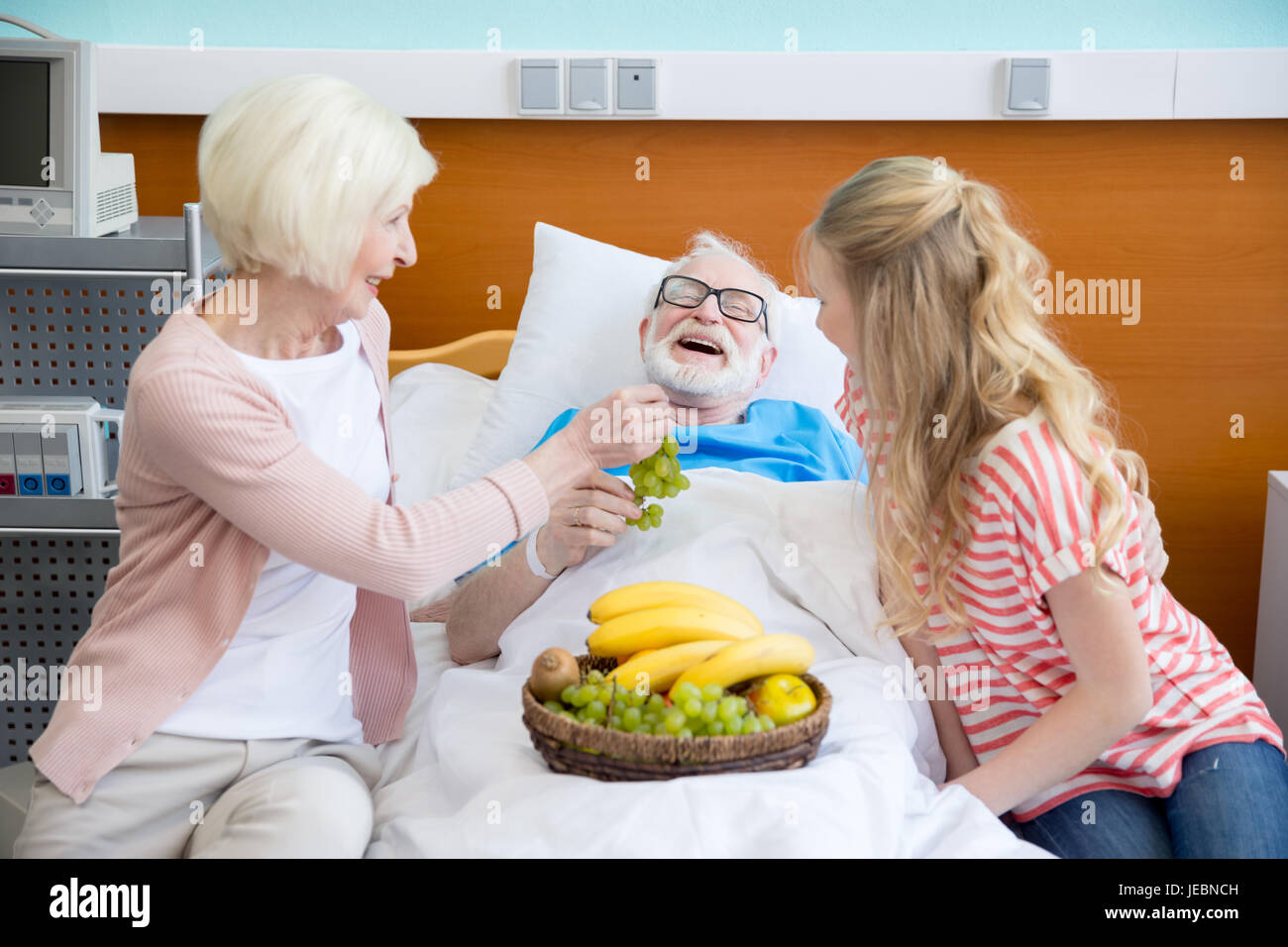 grandmother and granddaughter with fruits visiting patient in hospital. male patient in hospital bed concept - Stock Image