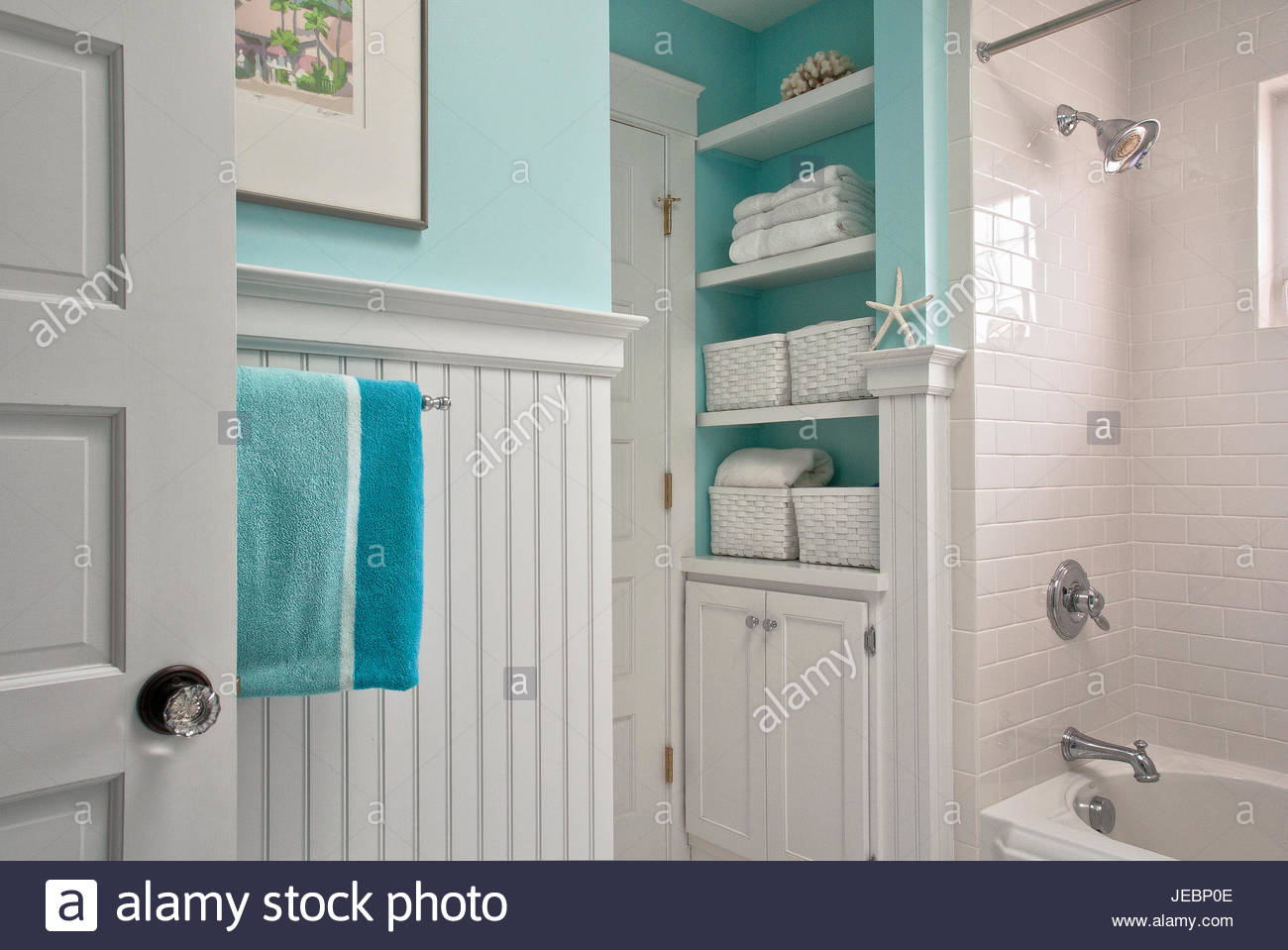 Beach inspired bathroom with aqua walls and towels and open shelving ...