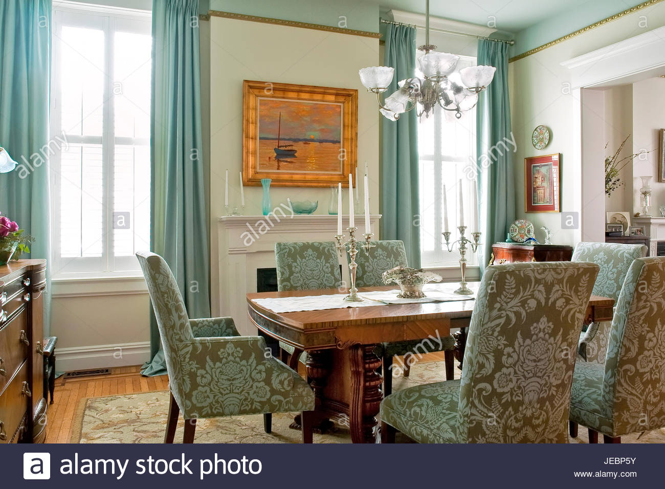 Dining room with Aqua drapes, wood table, sunset painting with Stock ...