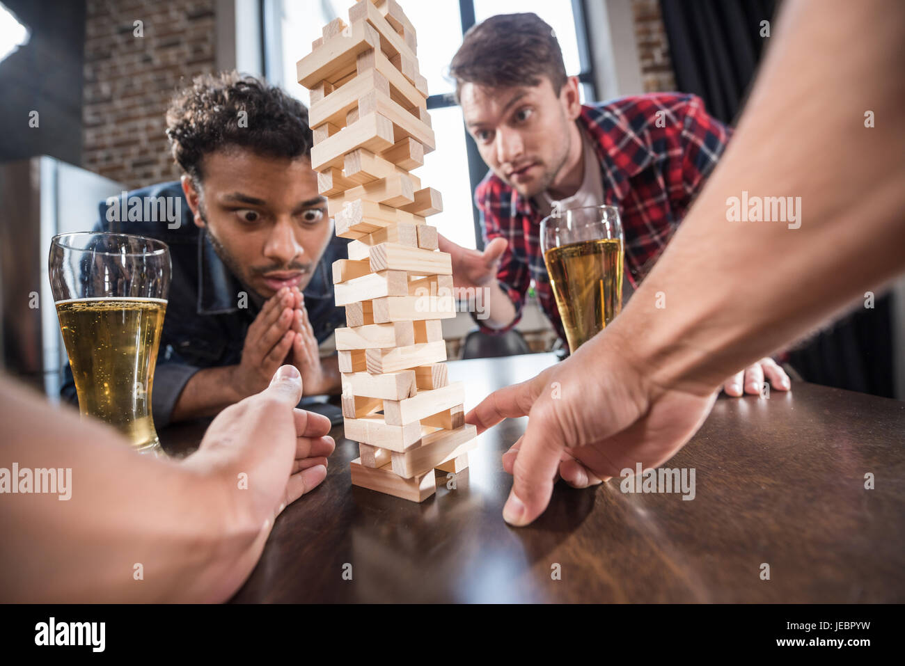 young men drinking beer and playing jenga game. young people having fun concept - Stock Image