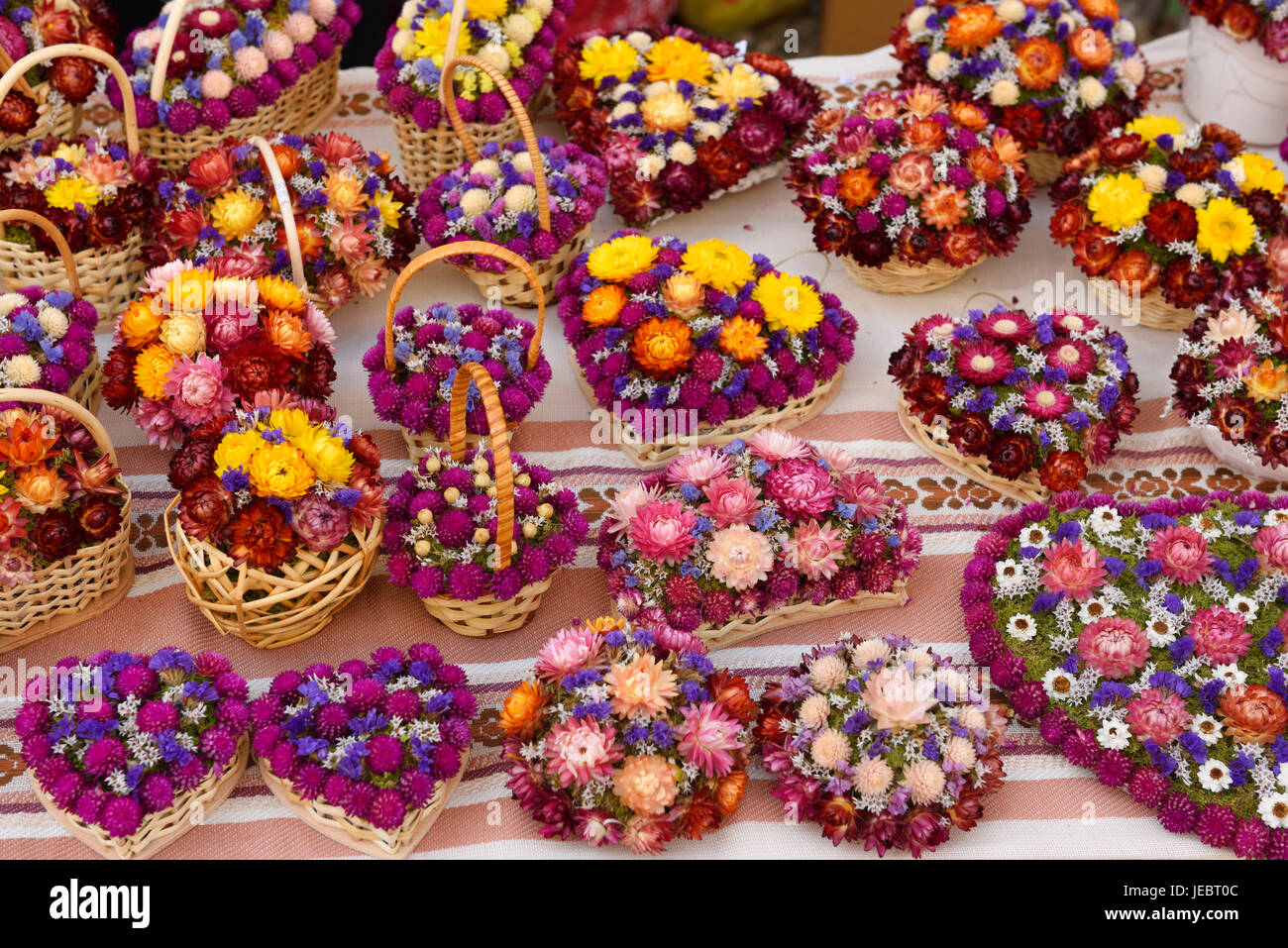Hand crafted dried pink purple and yellow flowers on a table at an open air stall at the Ljubljana Central Market - Stock Image
