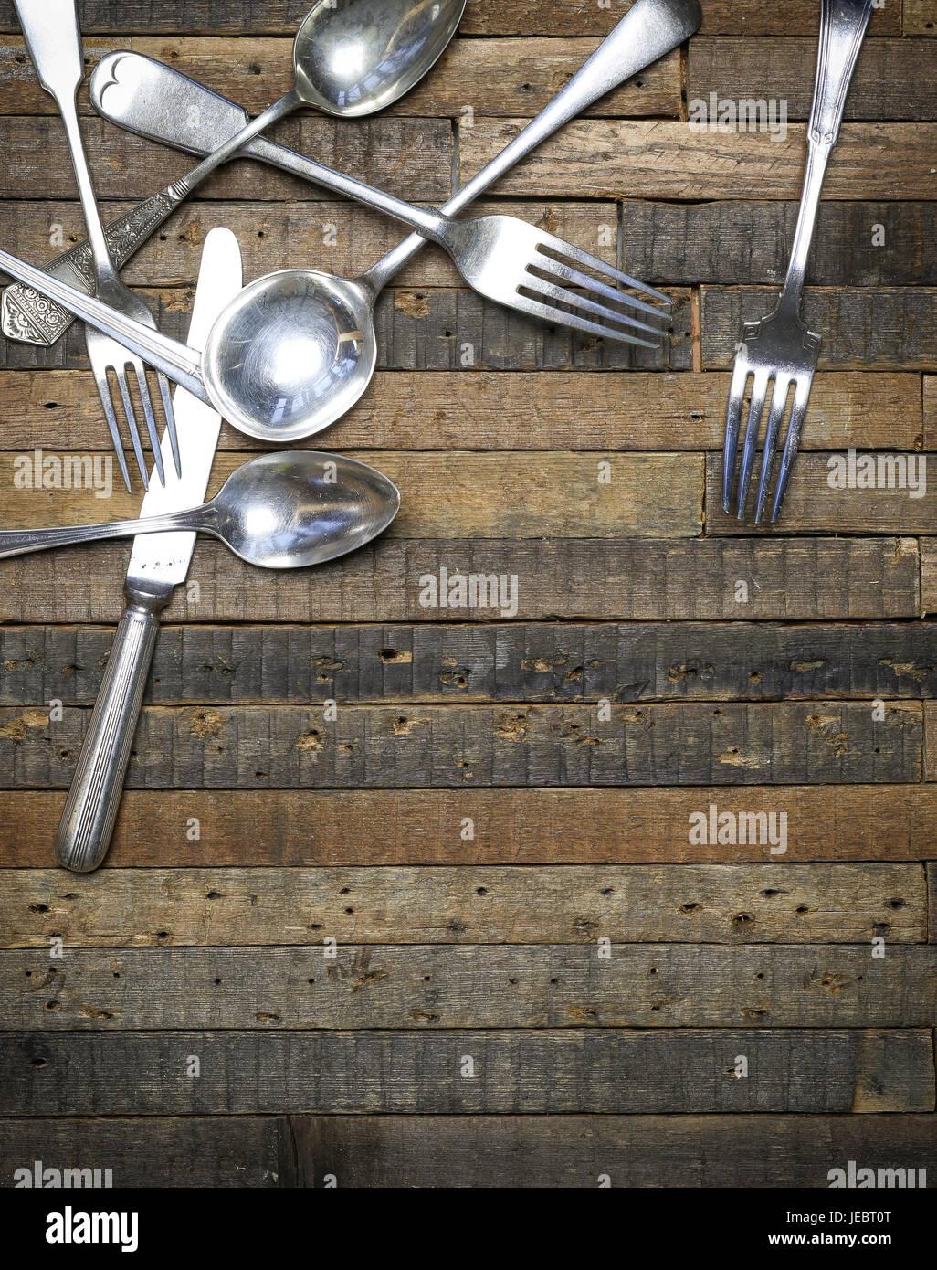 Vintage antique spoons forks and knifes on old wooden background flat lay food blog instagram mockup - Stock Image