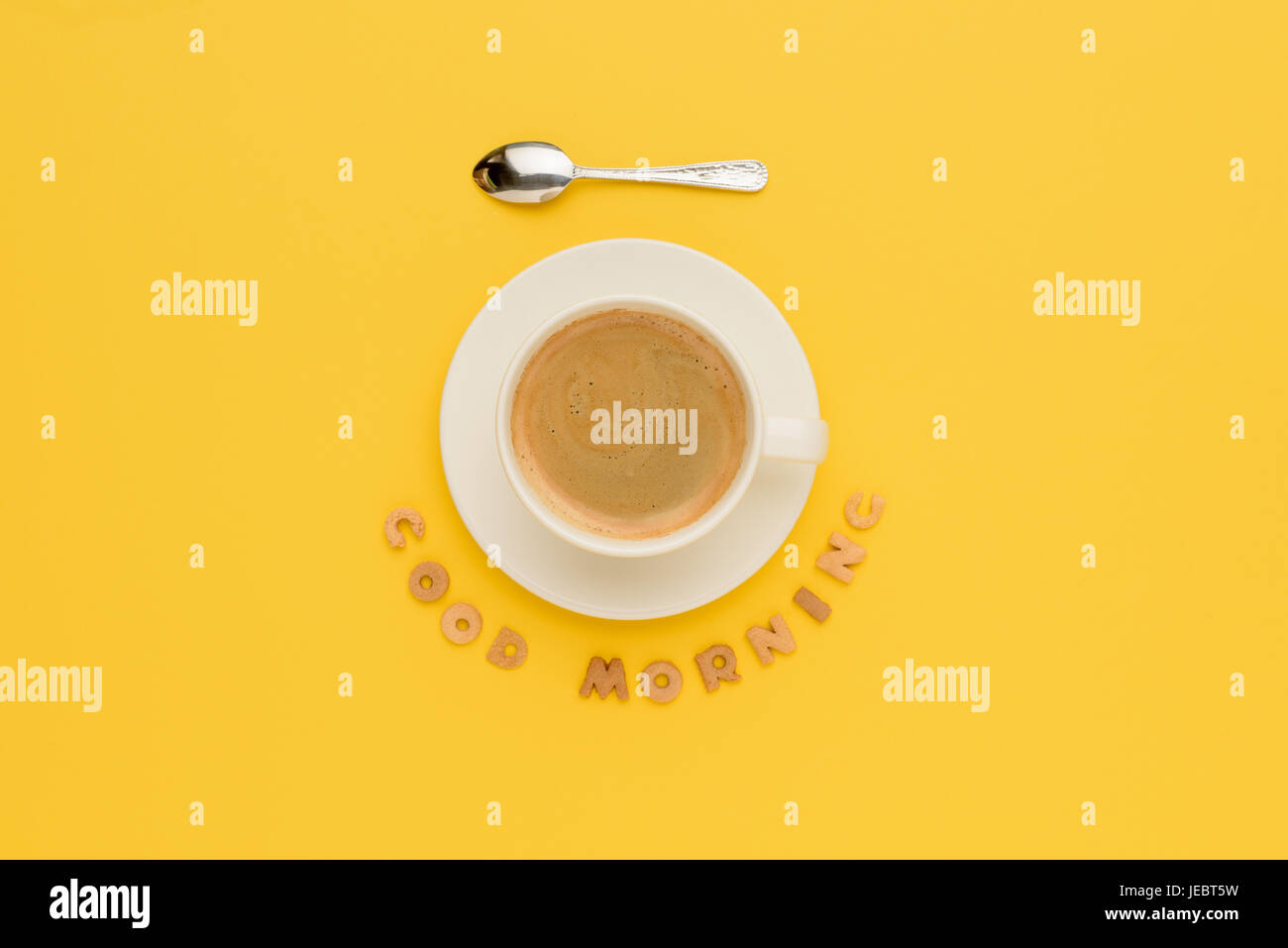 Top view of cup of fresh hot coffee and good morning inscription isolated on yellow - Stock Image