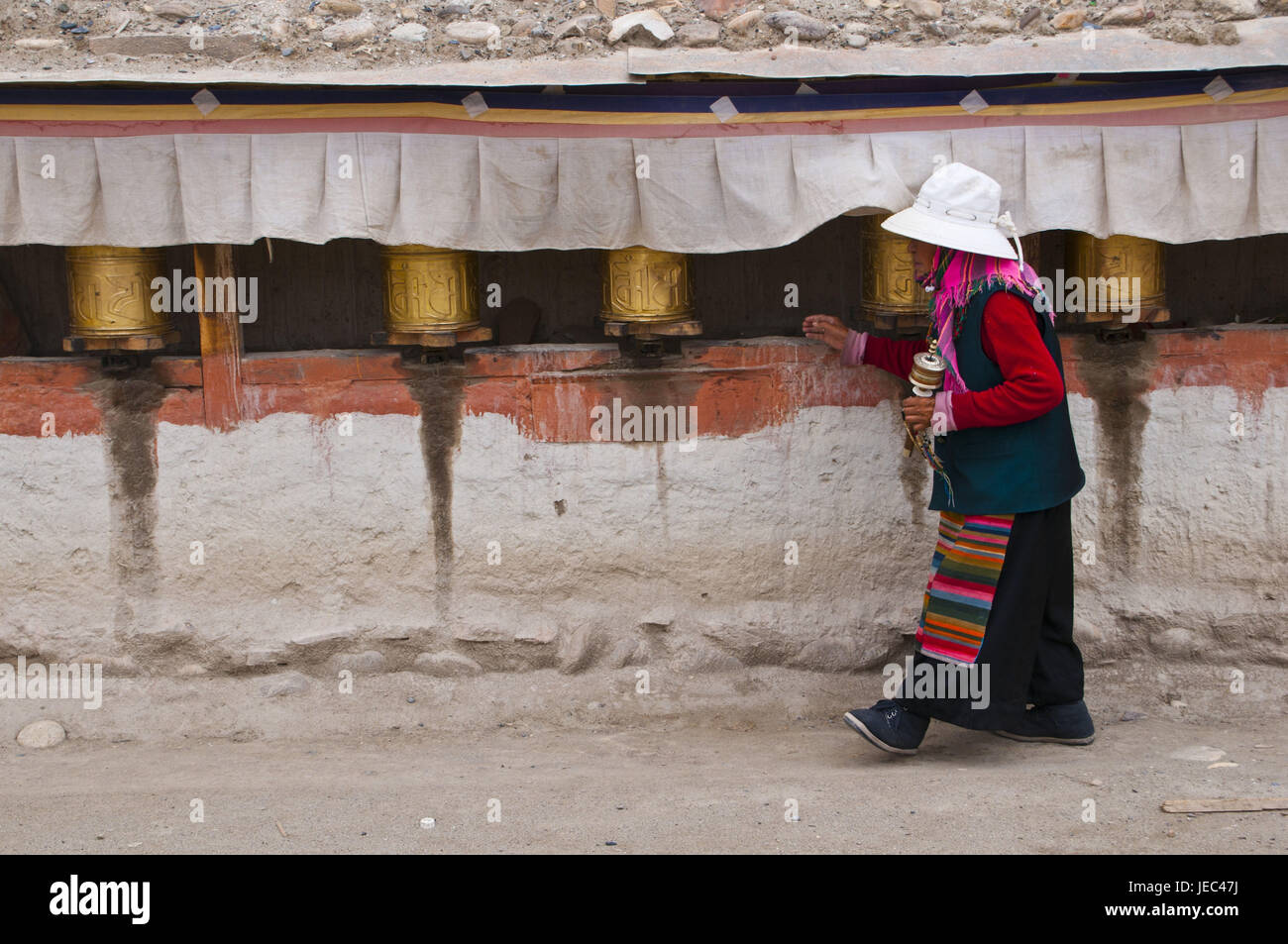 Old woman rotates the prayer drumming in the kingdom Guge, Westtibet, Asia, - Stock Image