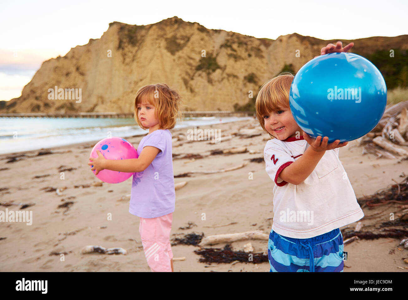 Children playing on the beach with balls Tolaga Bay (Māori: Uawa) - Stock Image