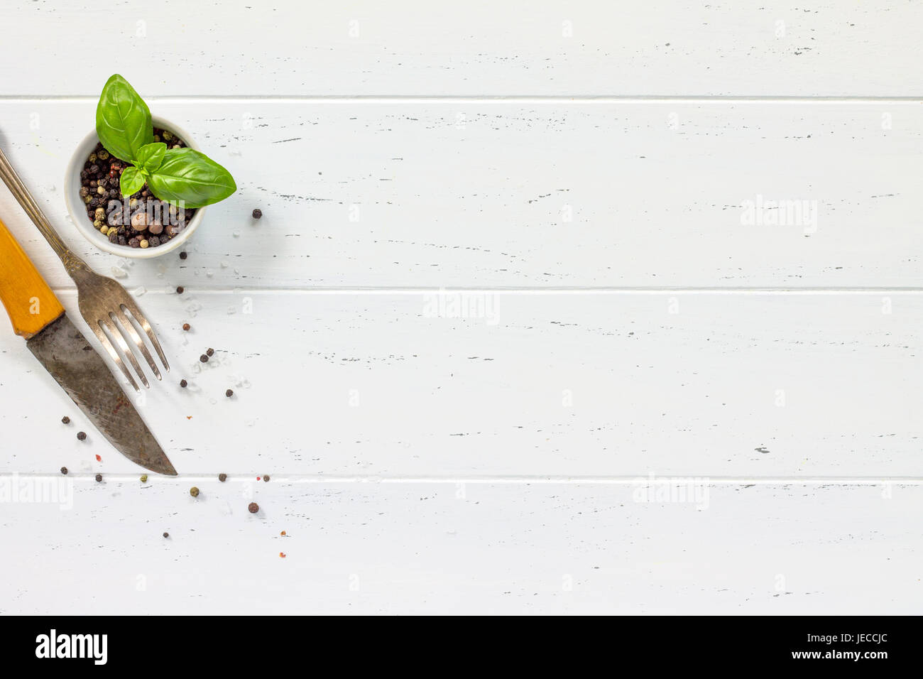 White wooden kitchen table. Background cooking with fresh herbs ...