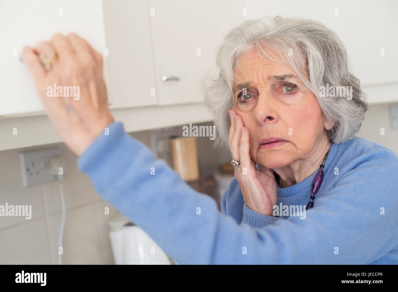 Forgetful Senior Woman With Dementia Looking In Cupboard - Stock Image