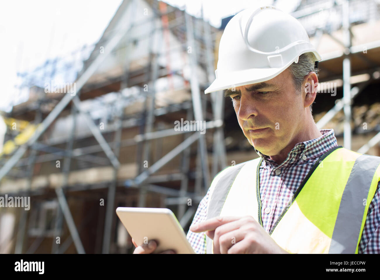 Architect On Building Site Using Digital Tablet - Stock Image