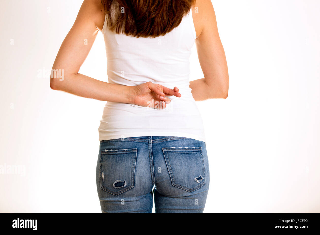 Dishonest woman telling lies, lying female holding fingers crossed behind her back - Stock Image